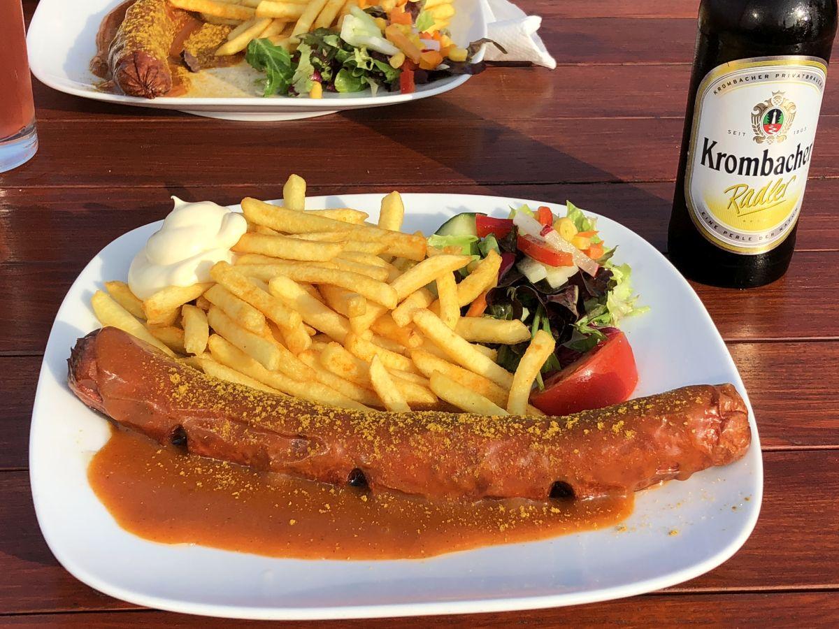 Currywurst mit Pommes und Radler am Surendorfer Strand